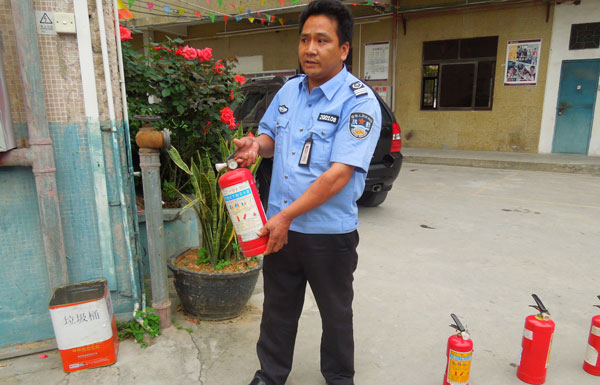The leader of the security team, Wande Chen, demonstrate the use of fire extinguishers.